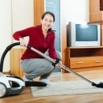 mature woman with vacuum cleaner on parquet floor